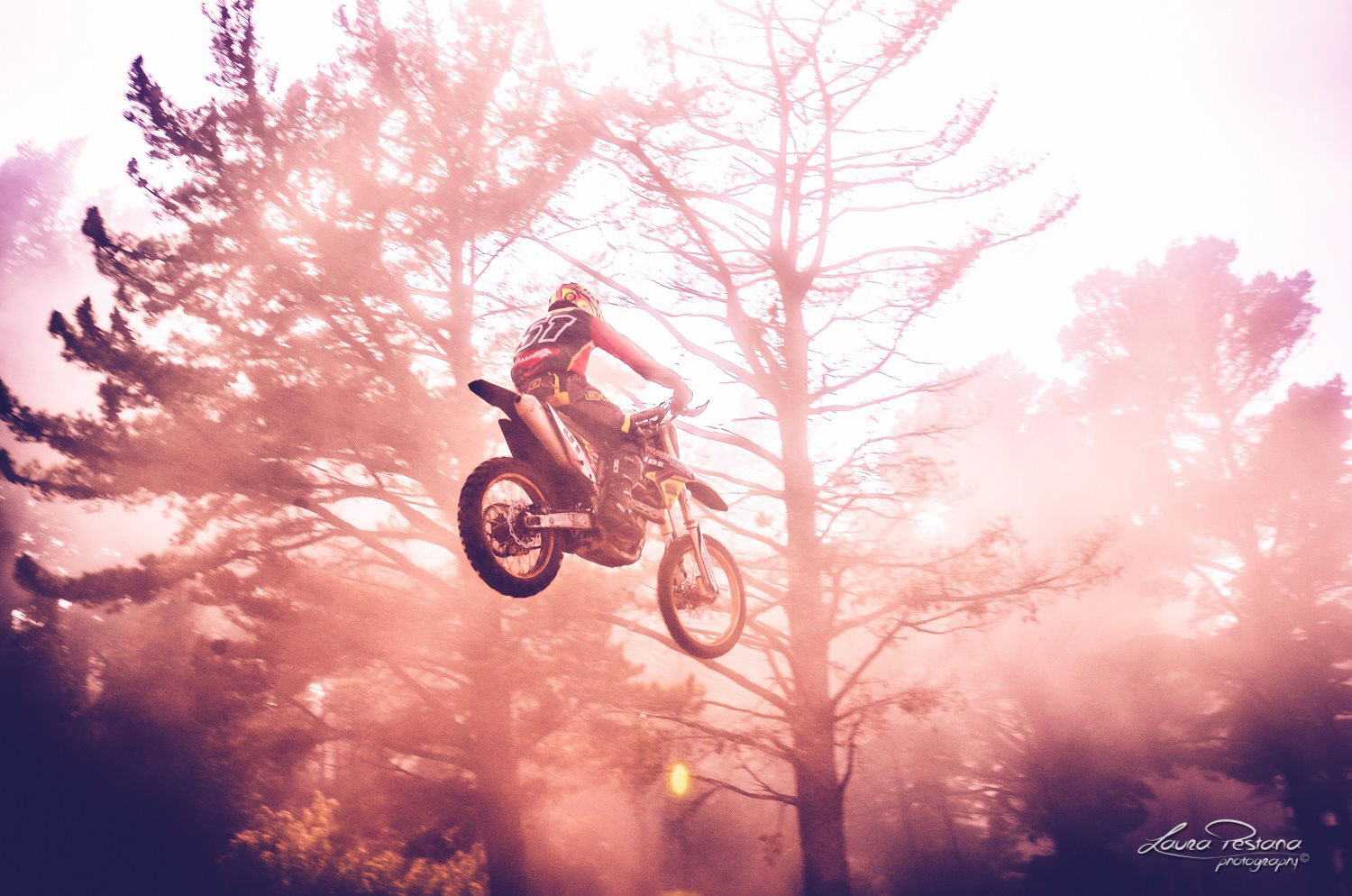 A photo of a rider jumping high with his dirt bike