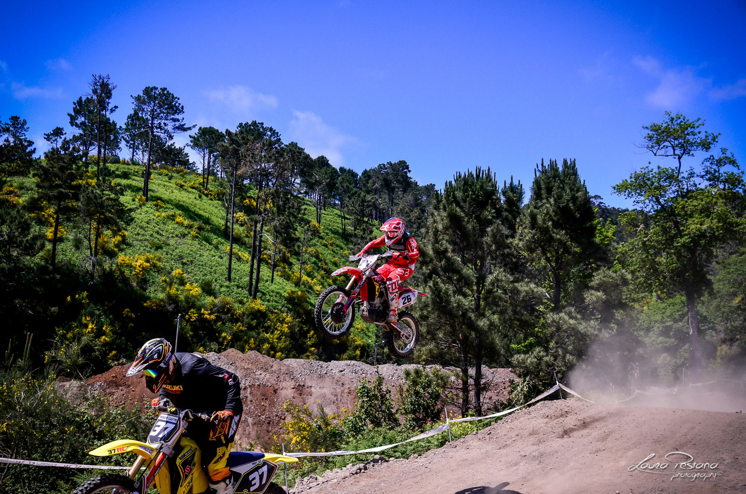 A rider jumping a double on a motocross track
