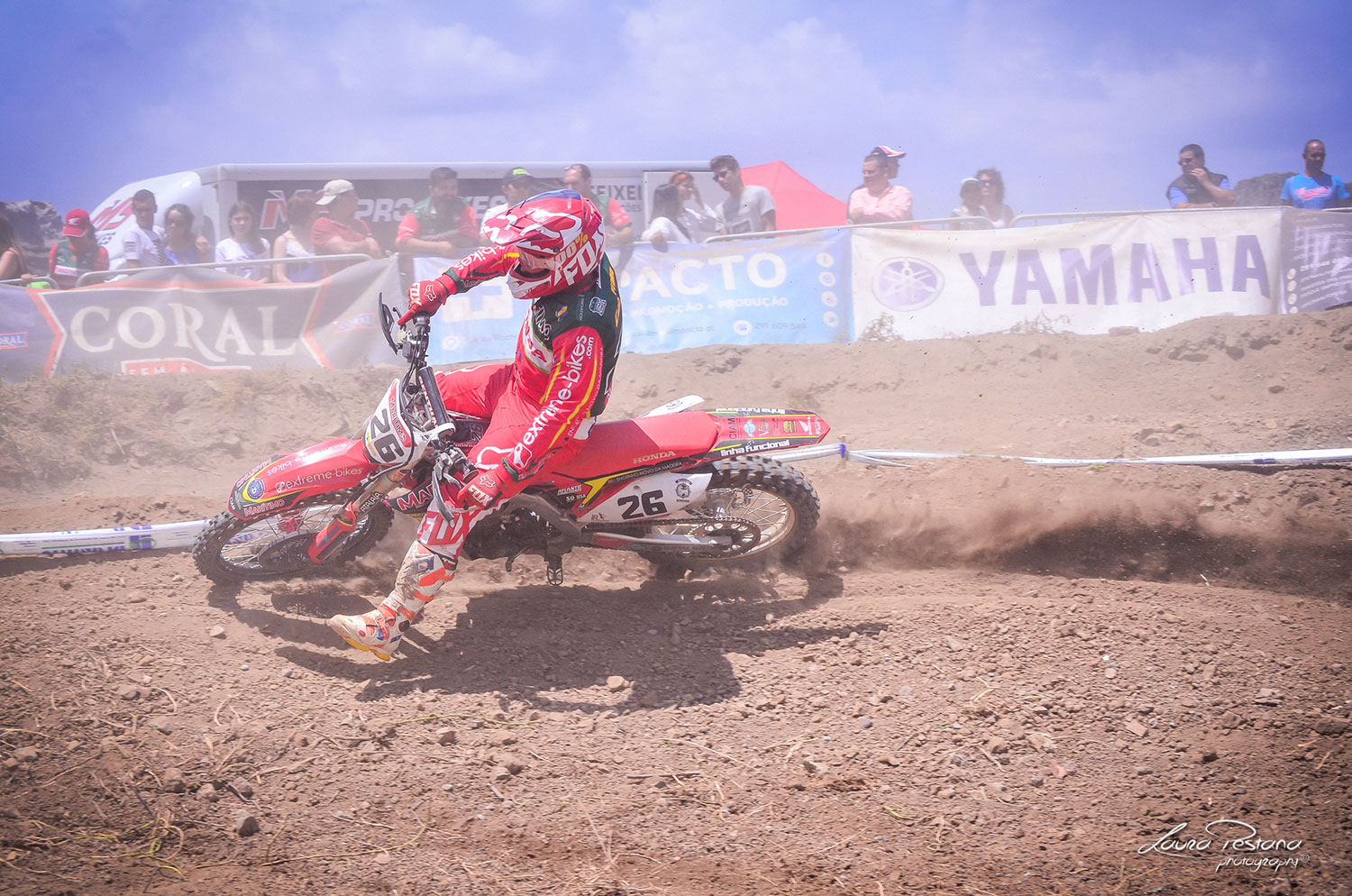 A rider making the berm on his honda crf on a motocross track