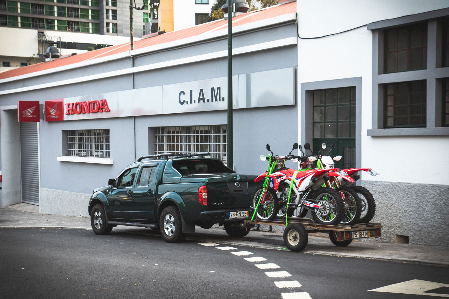 A parked navara with a trailer with 3 hondas crf 450 rx