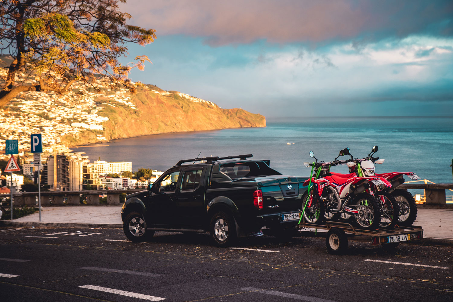 A Navara taking three hondas CRF450RX on a trailer parked up in Funchal